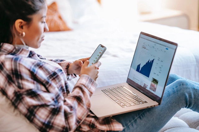 """Monitoring your channel growth is very important for knowing your current status and seeing what you need to improve and maintain. """"Crop ethnic trader with smartphone and laptop on bench indoors,"""" by """"Liza Summer"""" licensed under """"Pexels."""""""