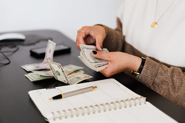 """For most YouTubers, including adverts in videos is the first step in making money from the platform. """"Crop payroll clerk counting money while sitting at table"""" by Karolina Grabowska license under """"Pexels."""""""