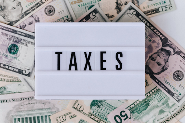 """Once you earn, you are now responsible for paying your taxes. """"Pile of American banknotes and retro light box,"""" by """"Karolina Grabowska"""" license under """"Pexels."""""""