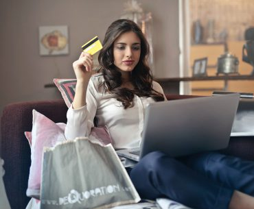 Woman holding a card while looking at her laptop. Video Overlay Ads are highly effective at getting your message in front of consumers who are ready to purchase.