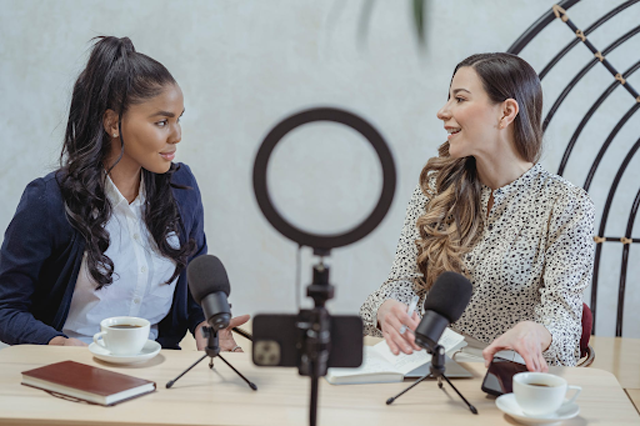 An interview is another type of content that creators do and post on Youtube. Image: Smiling woman interviewing black female guest and recording video by George Milton, licensed under Pexels.